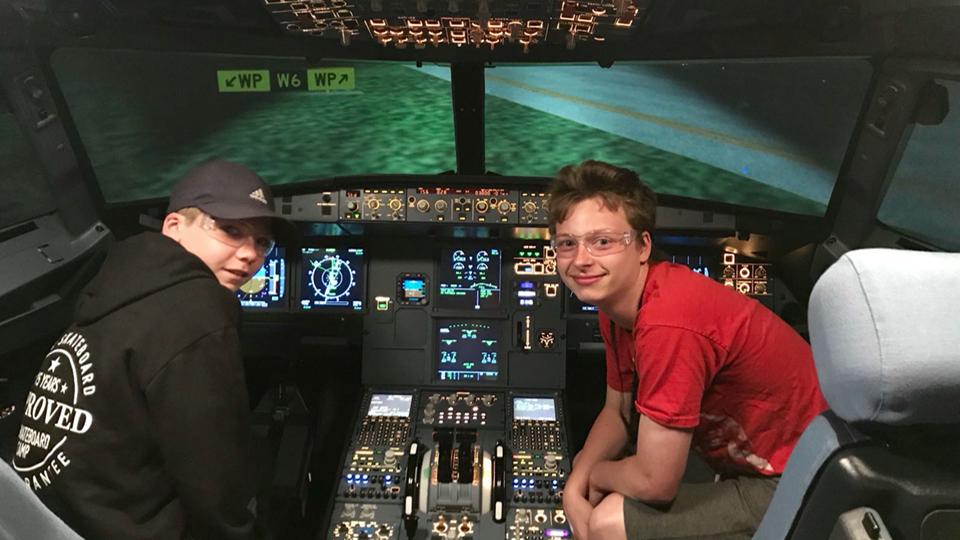 Des étudiants du programme «Driving Your Success» de la fondation Trioomph essaient un simulateur de vol